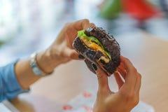 Hamburger noir dans sa main Images stock
