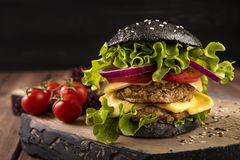 Hamburger noir de Vegan avec deux côtelettes, tomates, fromages, oignons et salades de pois chiche sur la table en bois, fond fon Photo stock