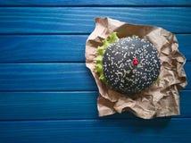 Hamburger noir et hamburger régulier avec des brochettes sous la forme de coeurs sur un fond en bois bleu Image stock