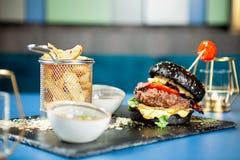 Hamburger noir savoureux avec des pommes frites sur la pierre noire Image stock