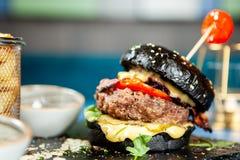 Hamburger noir savoureux délicieux de boeuf Image stock