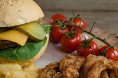 Hamburger, onion ring, cherry tomato and french fries on chopping board. Close-up of hamburger, onion ring, cherry tomato and french fries on chopping board Royalty Free Stock Images
