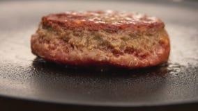Hamburger op de grill met keukenspatel die wordt weggeknipt stock footage