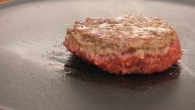 Hamburger op de grill met keukenspatel die wordt weggeknipt stock video