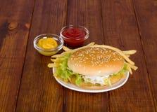 Hamburger op houten achtergrond met mosterd en Stock Afbeeldingen