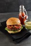 Hamburger op zwart servet met ketchup en mosterd Stock Afbeelding