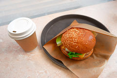 Hamburger in paper and takeaway coffee cup. Hot drink cup and tasty burger. Small breakfast in cafe Royalty Free Stock Photo