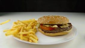 Hamburger para baixo nas microplaquetas de batata fritadas que caem, movimento lento, fast food, conceito da comida lixo vídeos de arquivo