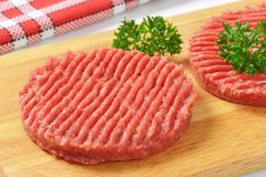 Hamburger patties. Detail of two raw hamburger patties with parsley on wooden cutting board Stock Photography