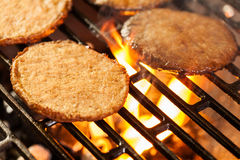 Hamburger patties on a grill with fire under Royalty Free Stock Photo
