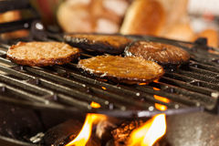 Hamburger patties on a grill with fire under Stock Photography