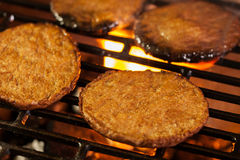 Hamburger patties on a grill with fire under Stock Image