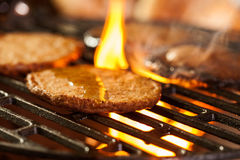 Hamburger patties on a grill with fire under Royalty Free Stock Photos