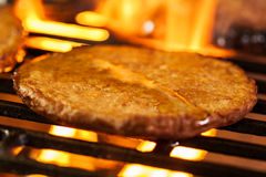 Hamburger patties on a grill with fire under Stock Images