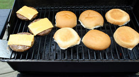 Hamburger patties with processed cheese slices cooking on an outdoor table top barbecue Stock Photos