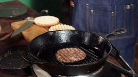 A hamburger patty frying on a cast iron grill. Stock footage. Hamburger Patty is prepared on the grill pan stock video