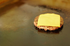 Hamburger patty frying on a grill with fresh cheese Stock Photos