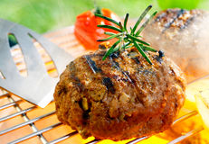 Grilled patty. Hamburger patty grilling on the barbecue isolated on Royalty Free Stock Photos