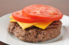 Hamburger patty with tomato and cheese Royalty Free Stock Photography
