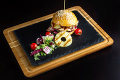 Hamburger with pineapple lies on a black slate surface-3 Royalty Free Stock Photography