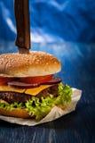 Hamburger pinned with knife Stock Photo