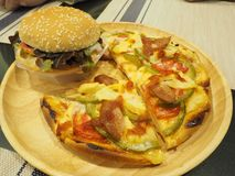 Hamburger and pizza on wood plate. In selective focus Royalty Free Stock Images