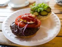 Hamburger on a plate, divided into halves, with a cutlet, tomatoes, pickles, ketchup and mustard. royalty free stock photo