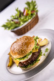Hamburger plate. Hamburger with fresh green salad and steak potatoes on a white table Royalty Free Stock Photography