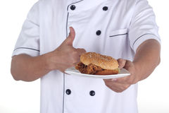 Hamburger on plate in hand of chef Royalty Free Stock Photo