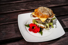 Hamburger on a plate. View of a hamburger on a plate with a flower of nasturtium Stock Image