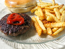 Hamburger Platter. Hamburger with catsup, french fries and roll on plate royalty free stock photos