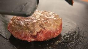 Hamburger podrzucał na grillu z kuchenną szpachelką zbiory