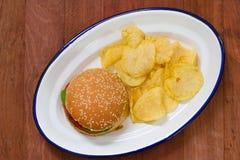 Hamburger with potato chips on white dish Stock Images