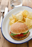 Hamburger with potato chips on white dish Royalty Free Stock Photos