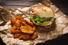Hamburger and potato wedges on wooden table Royalty Free Stock Photo