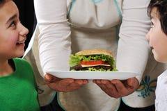 Hamburger prêt pour des enfants par la maman Photos libres de droits