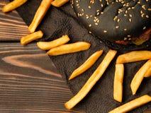 Hamburger preto com batatas fritas fotografia de stock