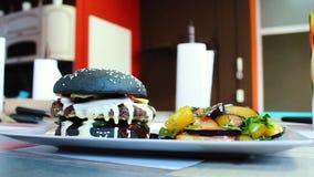 Hamburger pronto di manzo marmorizzato con i rotoli e l'insalata neri in salsa agrodolce video d archivio