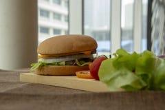 Hamburger przygotowywa z wieprzowiną, serem, pomidorami, sałatą i cebulami na prostokątnej drewnianej podłodze piec na grillu, zdjęcie stock