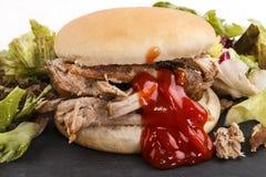 Hamburger with pulled pork, fresh healthy salad and ketchup Royalty Free Stock Image