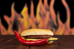 Hamburger and red hot pepper on  background of flames. Royalty Free Stock Images