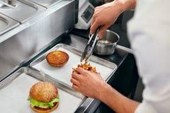 Hamburger restauracja Zbliżenie szefa kuchni Kulinarni hamburgery W kuchni zdjęcia stock