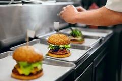 Hamburger restauracja Zbliżenie szefa kuchni Kulinarni hamburgery W kuchni obraz royalty free
