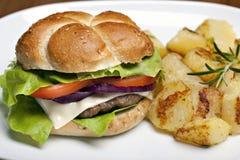 Hamburger with roasted potatoes Stock Images