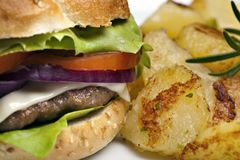 Hamburger with roasted potatoes Stock Images