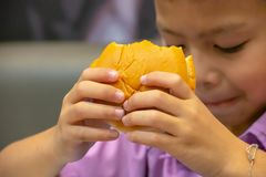 Hamburger ryba w ręki Asia chłopiec trzyma łasowanie zdjęcia stock