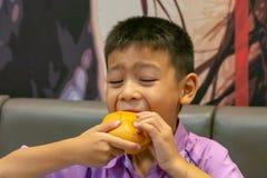 Hamburger ryba w ręki Asia chłopiec trzyma łasowanie zdjęcia royalty free