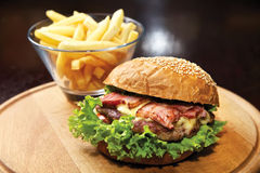 Hamburger saboroso com carne e bacon na placa Fotografia de Stock Royalty Free