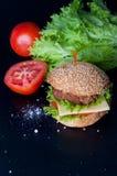 Hamburger with salad, tomato, meat on black  backdrop Royalty Free Stock Photography