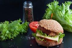 Hamburger with salad, tomato, meat on black  backdrop Stock Photo